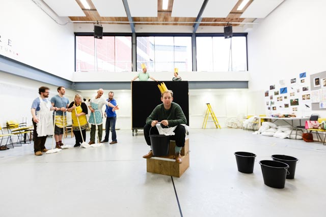 Photo of a rehearsal room. One man sits in the middle of the frame wearing a crown and five others stand on the side holding mops.