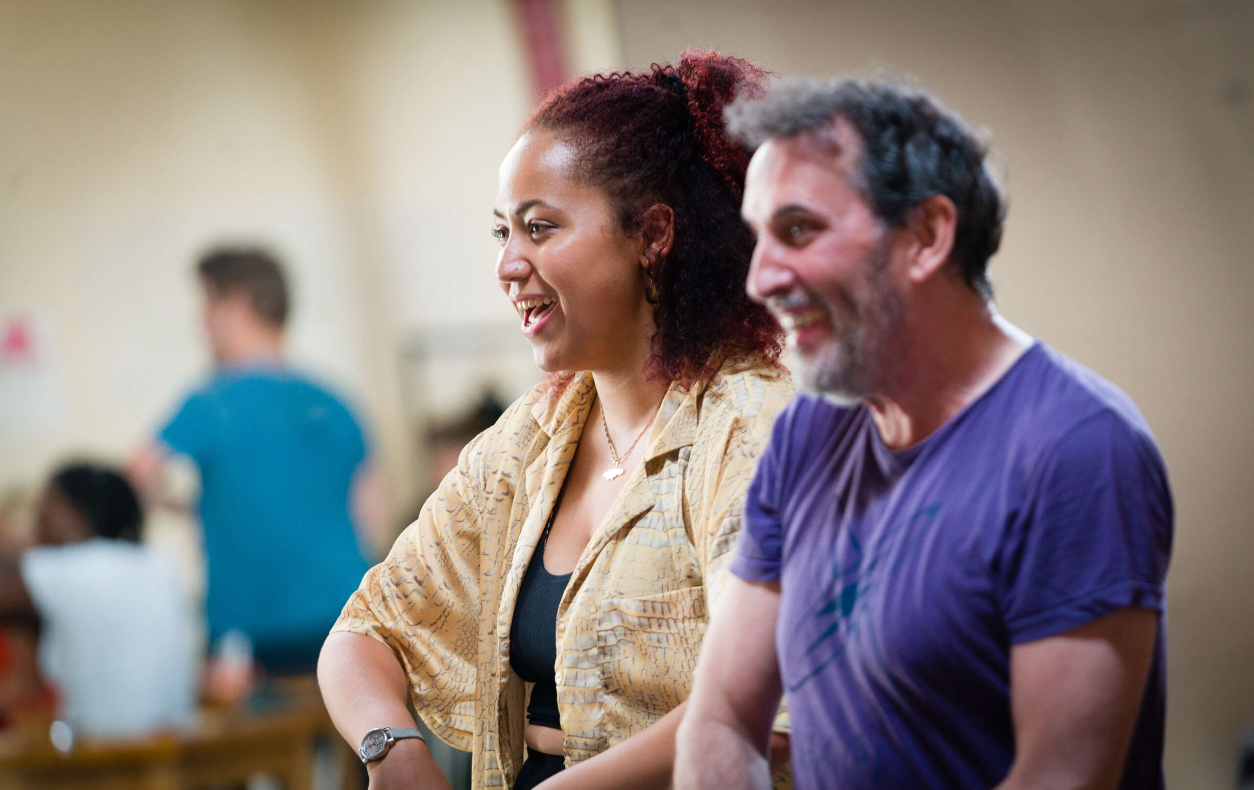 A young woman and man smiling in a rehearsal room